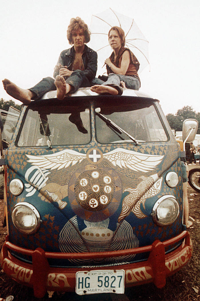 Concert-goers sit on the roof of a Volkswagen bus at the Woodstock Music and Arts Fair at Bethe ...
