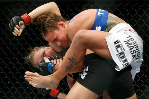 Liz Carmouche, top, grapples with Ronda Rousey during their UFC 157 women's bantamweight champi ...