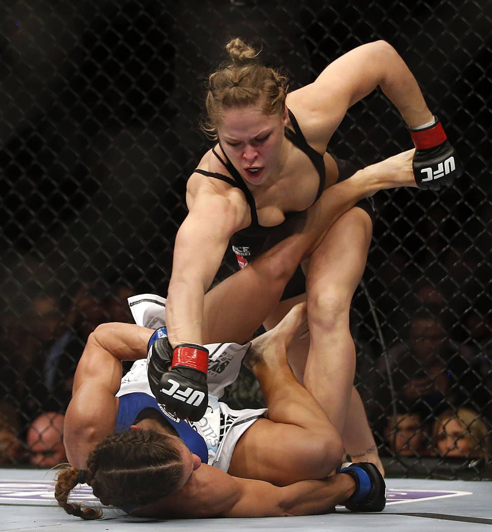 Ronda Rousey, top, punches Liz Carmouche during their UFC 157 women's bantamweight championship ...