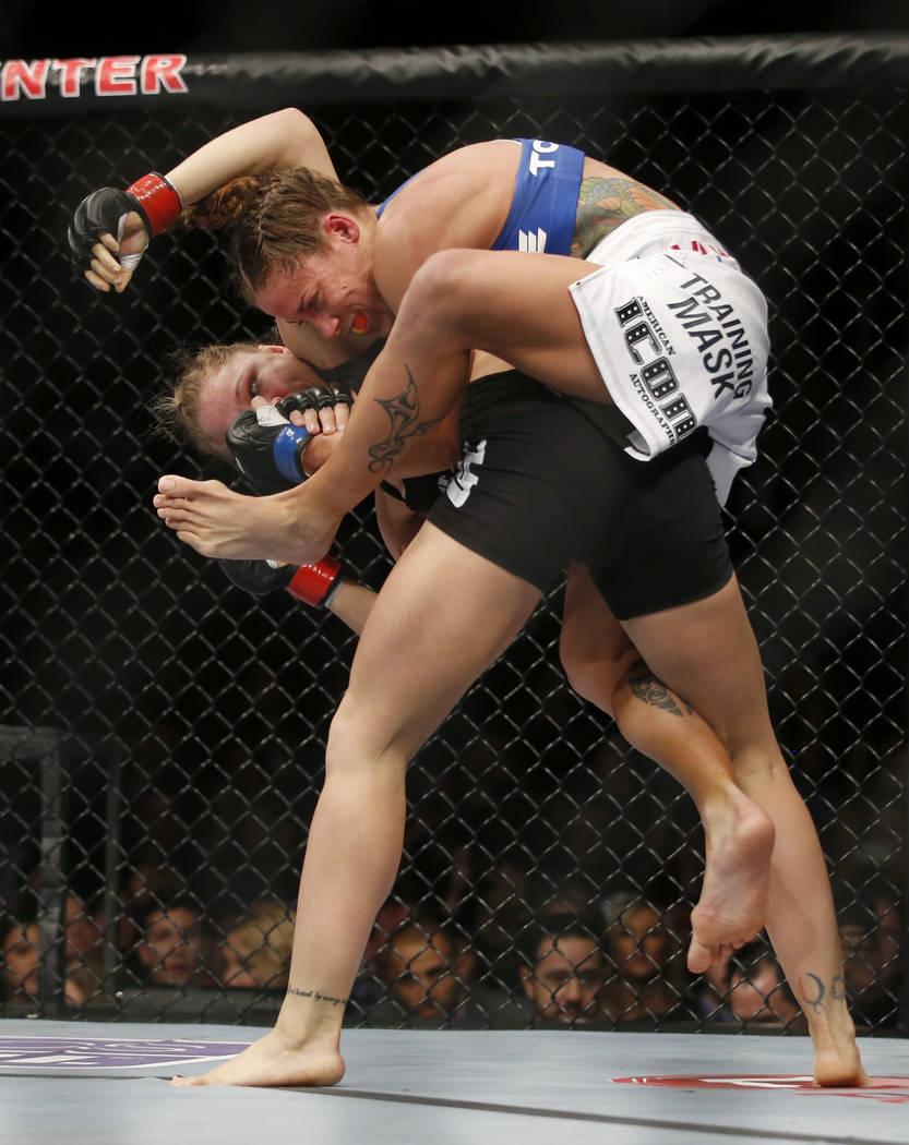 Liz Carmouche, top, tries to choke Ronda Rousey during their UFC 157 women's bantamweight champ ...