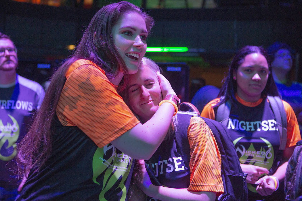Lauryn Landkrohn 22, hugs fellow Knightsec teammate Sydney Munro, 23, both from the University ...