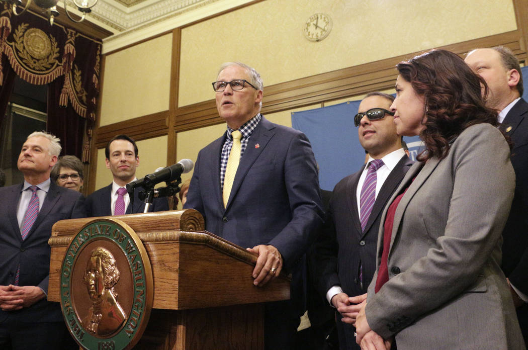 FILE - In this April 29, 2019, file photo, Gov. Jay Inslee, surrounded by Democratic lawmakers ...