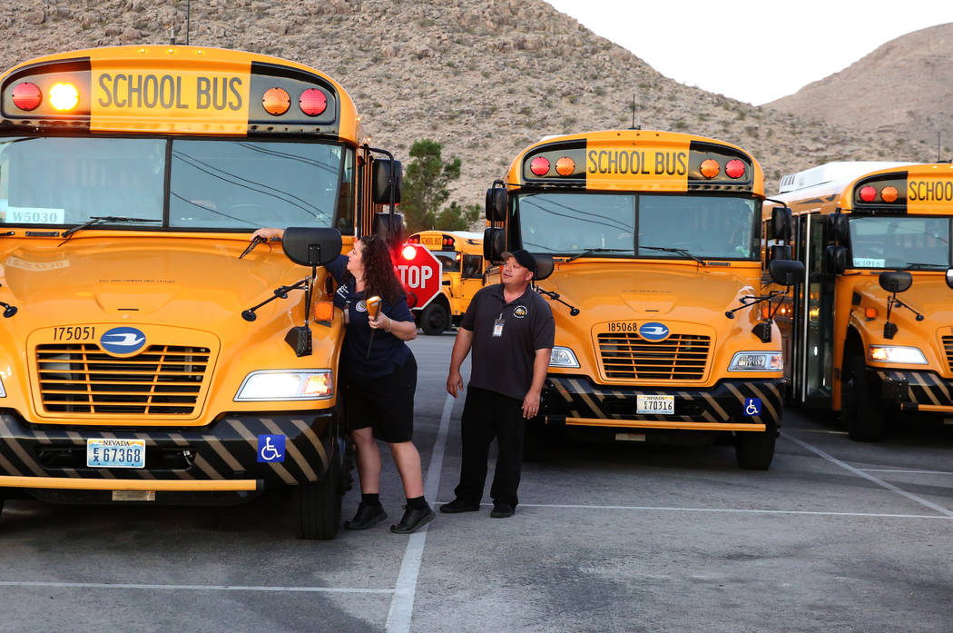 Clark County School District bus driver Christy Mattson inspects her bus as her supervisor Kevi ...