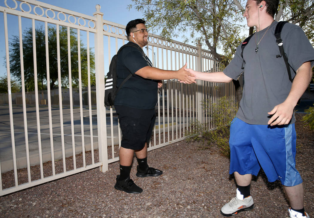 Sunrise Mountain High School junior Bryan Mungia, left, greets a friend who declined to give hi ...