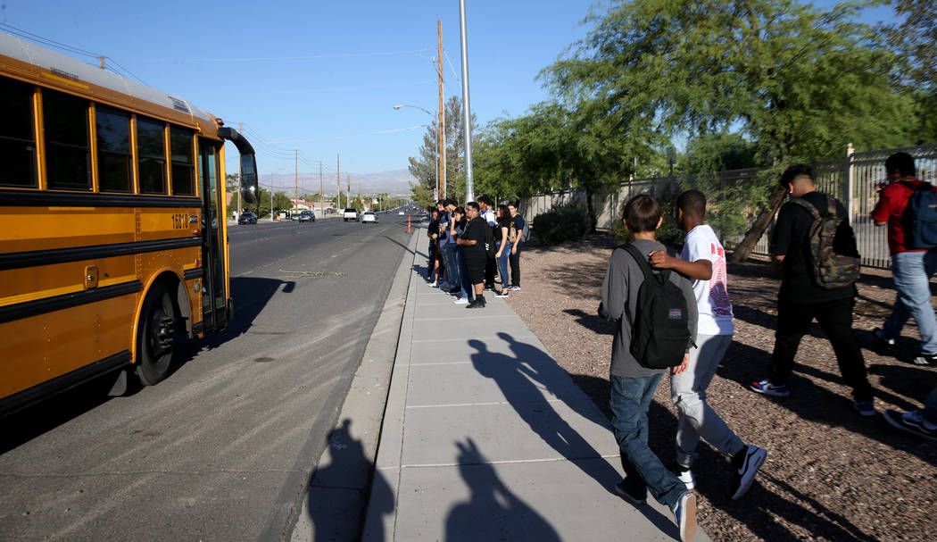 Sunrise Mountain High School students prepare to board the school bus at East Owens Avenue and ...