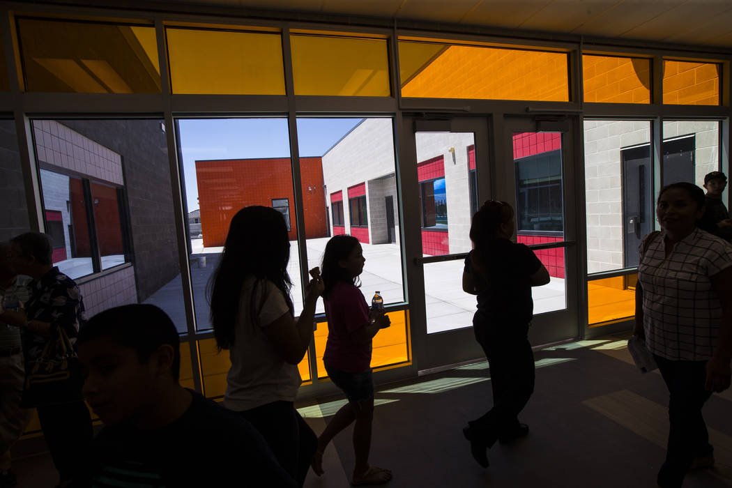 Families roam the hallways after a ribbon-cutting ceremony for Earl Jenkins Elementary School i ...