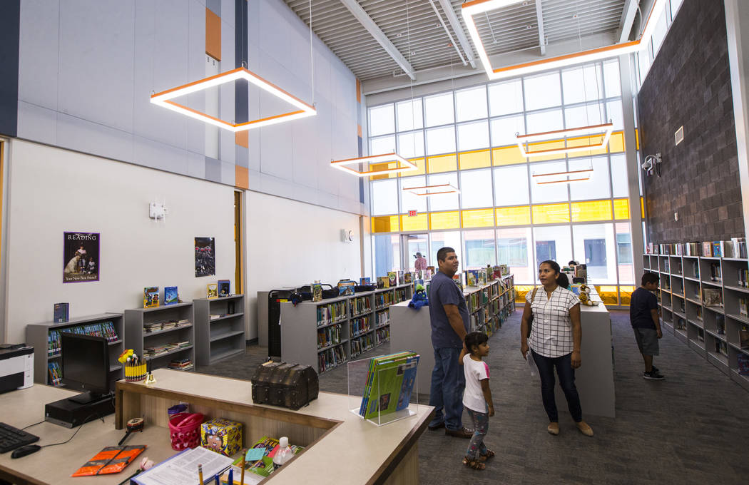 A family checks out the library after the ribbon-cutting ceremony for Earl Jenkins Elementary S ...