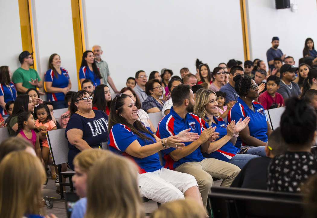 Teachers, center, are cheered on during a ribbon-cutting ceremony for Earl Jenkins Elementary S ...