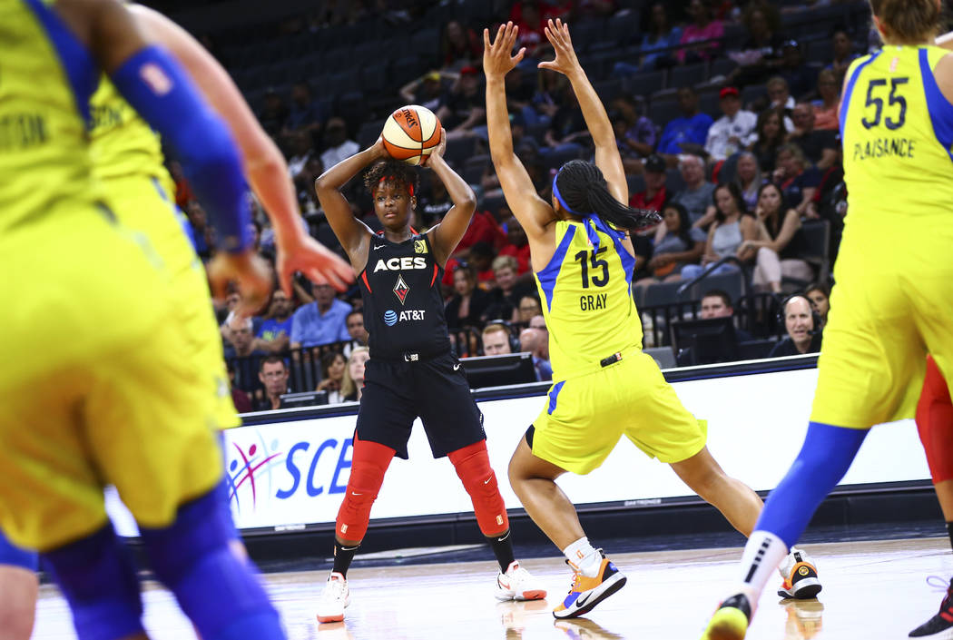 Las Vegas Aces' Sugar Rodgers looks to pass the ball under pressure from Dallas Wings' Allisha ...