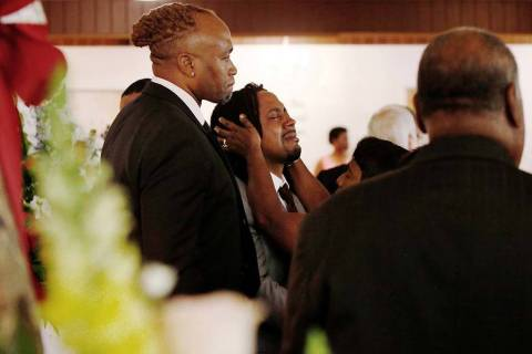 A relative attempts to console Dion Green, center, before the funeral for his father, Derrick F ...