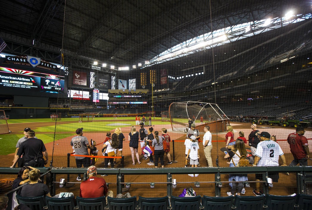 Baseball fans with early access watch teams practice before an Arizona Diamondbacks baseball ga ...