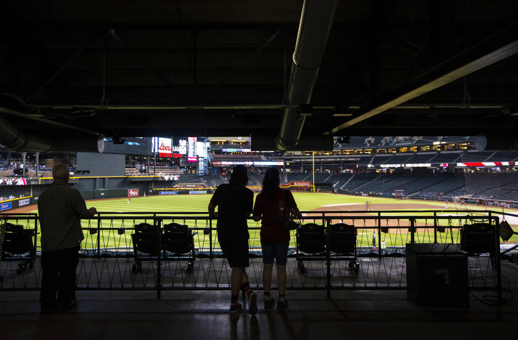 Baseball fans watch teams practice before an Arizona Diamondbacks baseball game against the Phi ...