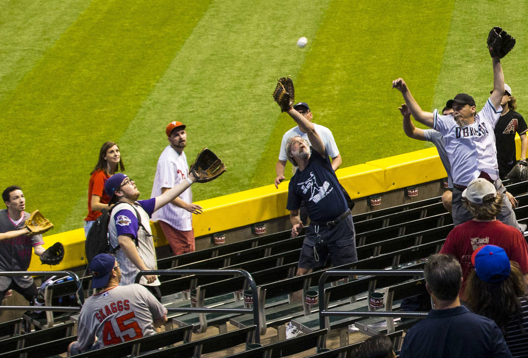 Baseball fans jump for the ball as teams practice before the start of an Arizona Diamondbacks b ...