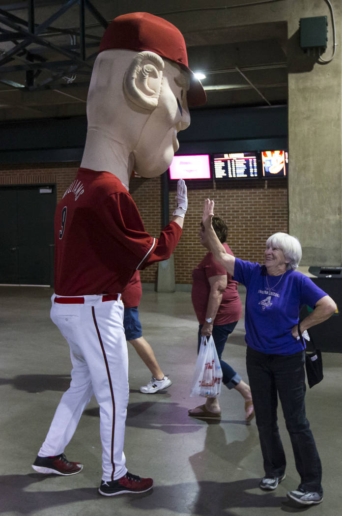 Cindy McBride, of Phoenix, high-fives the oversized mascot representing Diamondbacks' Matt Will ...