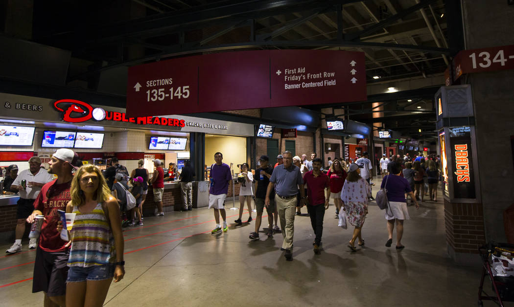 Fans walk the concourse before the start of an Arizona Diamondbacks baseball game against the P ...