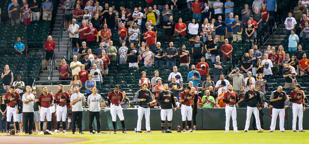 Members of the Arizona Diamondbacks stand for the national anthem before playing the Philadelph ...
