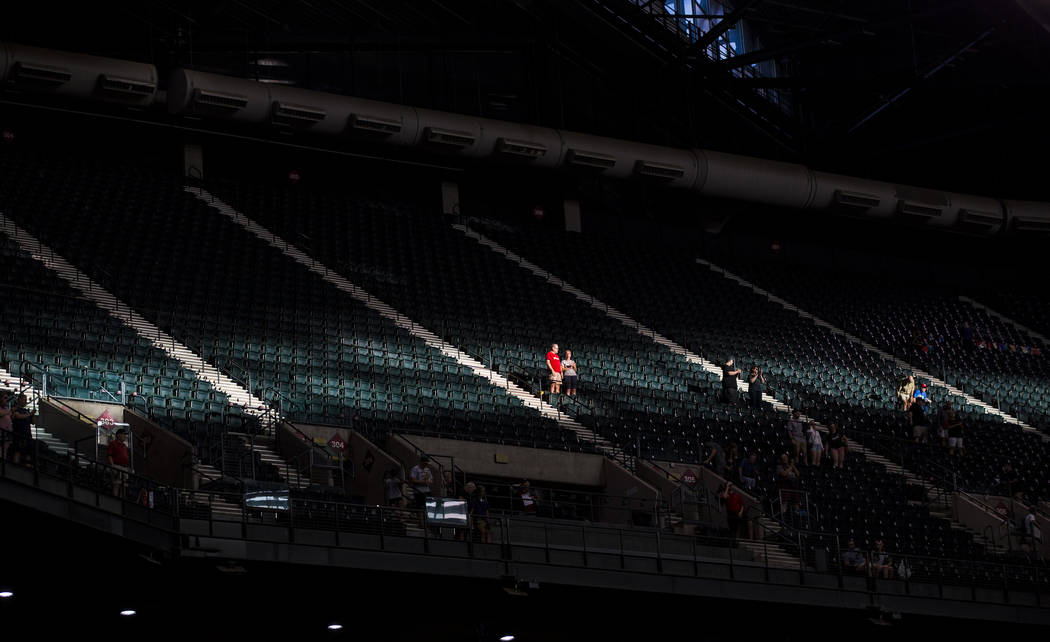 Fans are highlighted by a strip of sunlight before the start of an Arizona Diamondbacks basebal ...