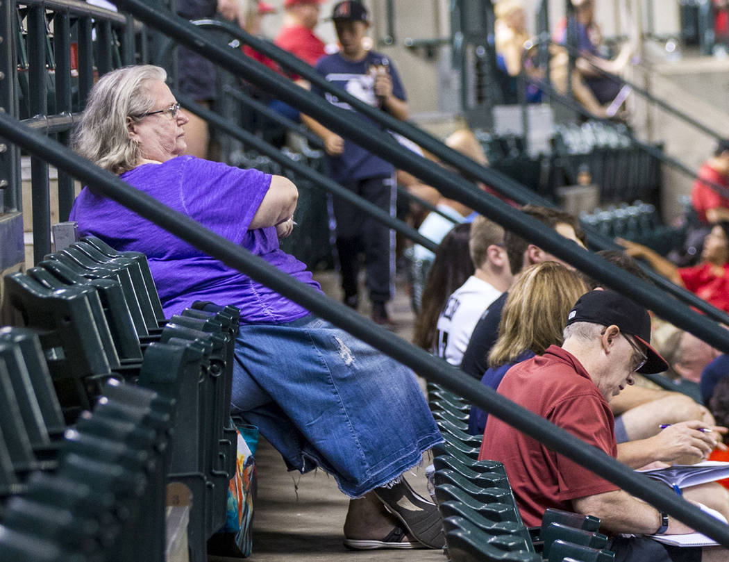 Jackie Laird, of Phoenix, in purple, watches the action during an Arizona Diamondbacks baseball ...