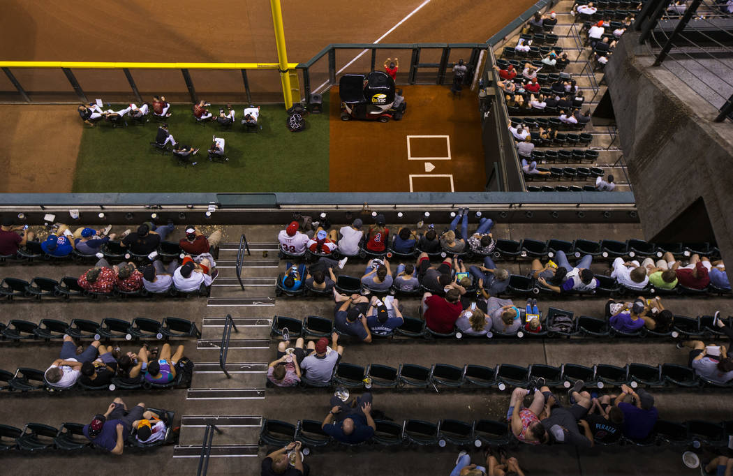 Fans watch the action as members of the Arizona Diamondbacks sit in the bullpen during a baseba ...