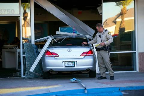 Las Vegas police investigate the scene where a driver in a car crashed into an AT&T store i ...