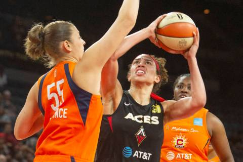 Las Vegas Aces forward Dearica Hamby, center, goes to the hoop against Connecticut Sun center T ...