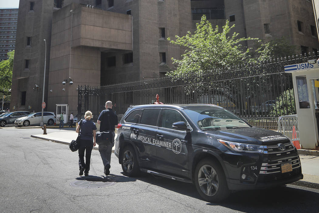 New York City medical examiner personnel leave their vehicle and walk to the Manhattan Correcti ...