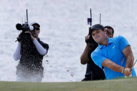 Patrick Reed hits out of a bunker on the fourth hole in the final round of the Northern Trust g ...