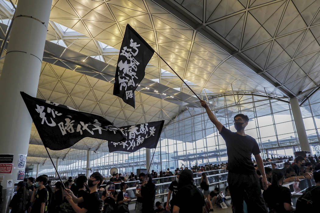 Protesters wave flags at the Hong Kong International Airport, Monday, Aug. 12, 2019. One of the ...