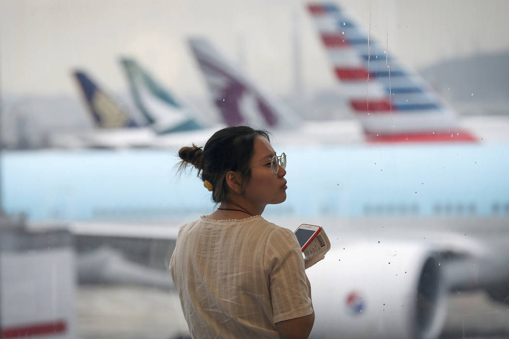 A woman reacts as airplanes are parked at the Hong Kong International Airport, Monday, Aug. 12, ...