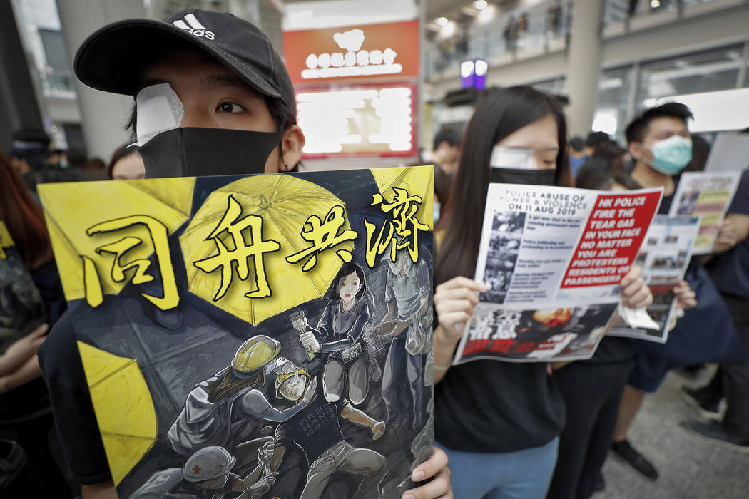Protesters wear eyepatch during a protest at the arrival hall of the Hong Kong International Ai ...