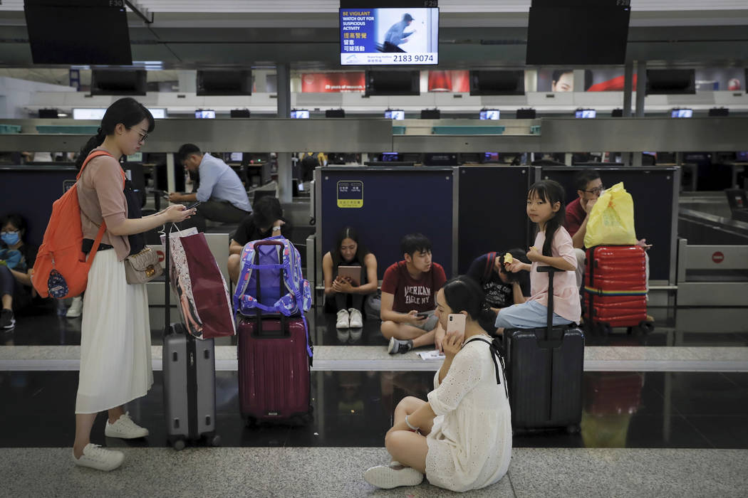 Travelers gather at the closed check-in counters as protesters stage a protest at the Hong Kong ...