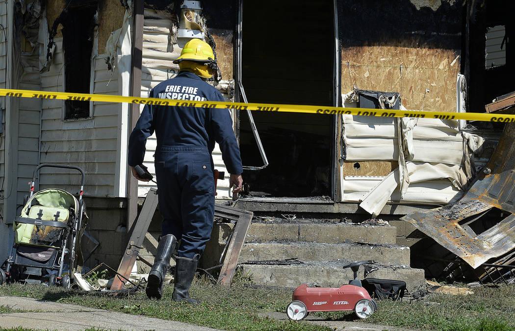 Erie Bureau of Fire Inspector Mark Polanski helps investigate a fatal fire in Erie, Pa, on Sund ...
