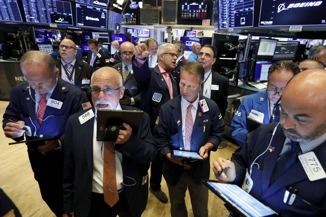 Traders work on the floor of the New York Stock Exchange, Monday, Aug. 12, 2019. Stocks are edg ...