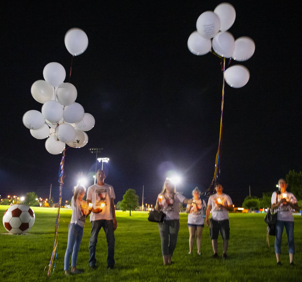 Mourners release balloons during a candlelight vigil for Harlee Deborski and Timothy Bailey at ...