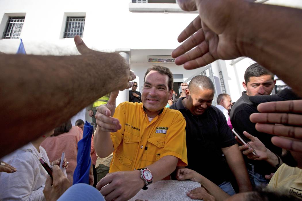 FILE - In this Dec. 9, 2015 file photo, reelected opposition congressman Tomas Guanipa greets s ...