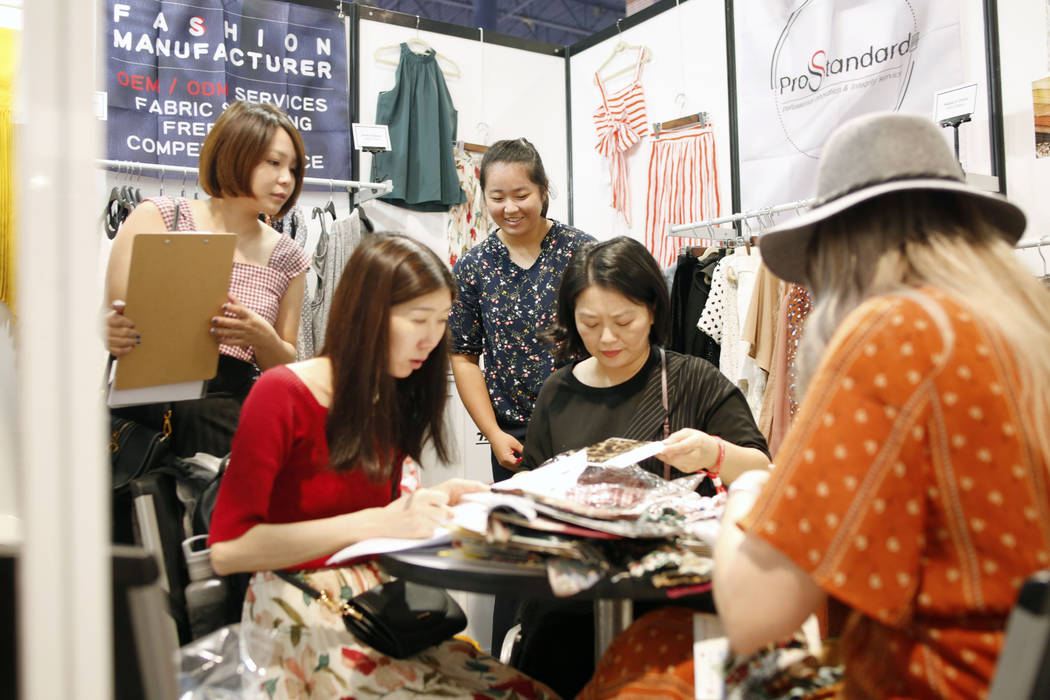 A consumer looks at fabric swatches from the Prostandard Co., LTD booth during the first day of ...