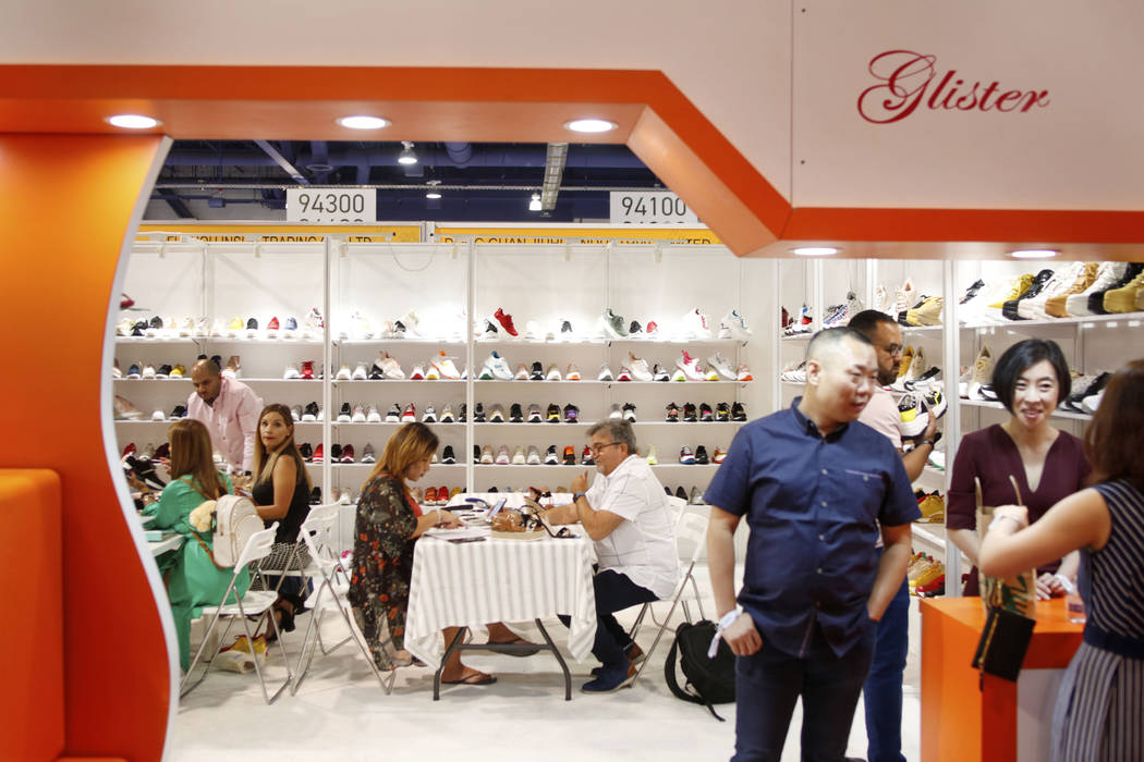 Consumers speak with exhibitor Elite Footwear during the first day of the MAGIC trade show at t ...