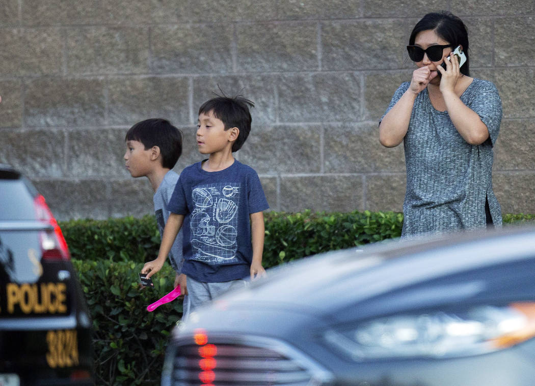 A woman and her two children stand near the scene where a shootout near a freeway killed a Cali ...