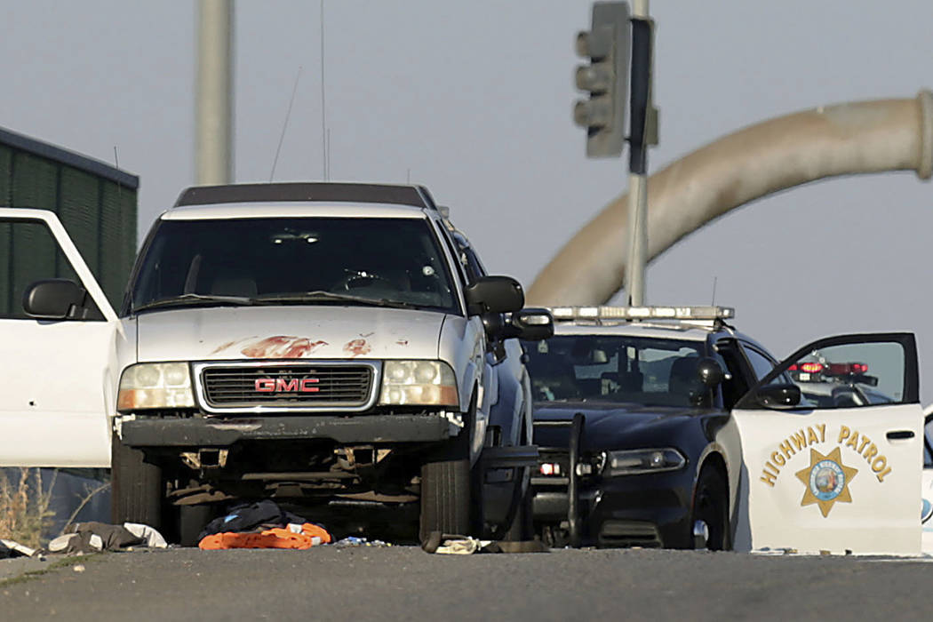 Authorities investigate the scene on the Eastridge Avenue overpass over Interstate 215, where a ...