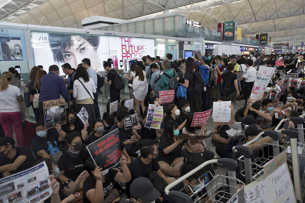 Travelers walk past as protesters hold a sit-in rally near the departure gate of the Hong Kong ...