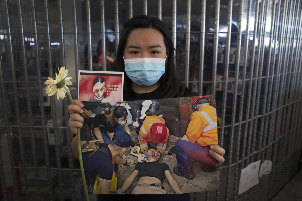 A woman holds a flower and posters showing people injured by police as protesters stage a sit-i ...