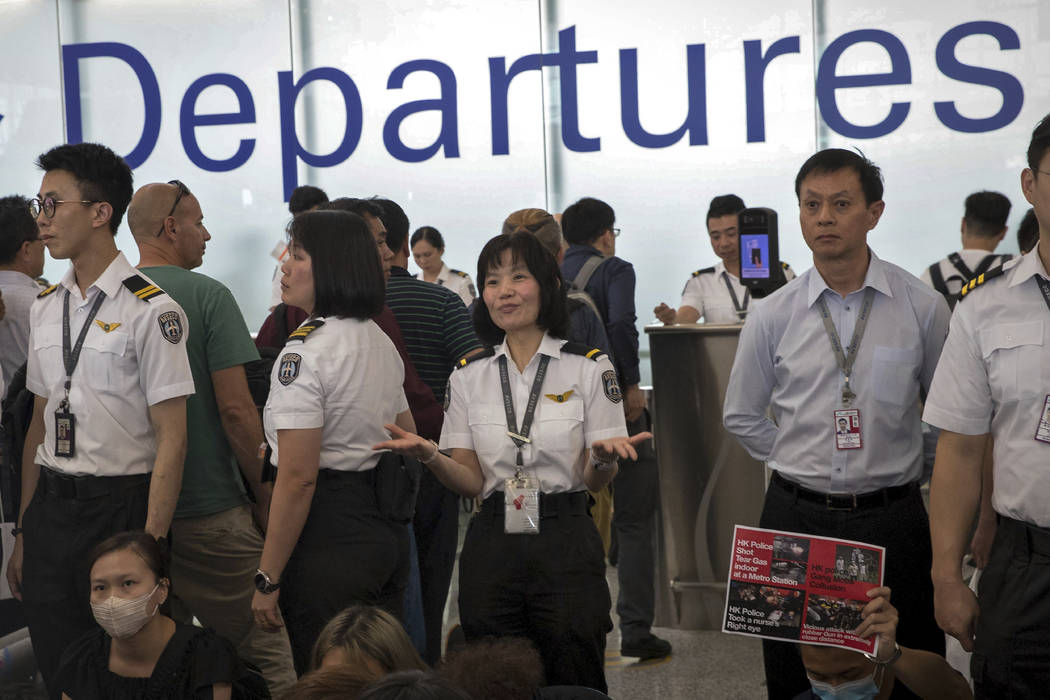 An airport security staff member gestures to travelers at the Hong Kong International Airport i ...
