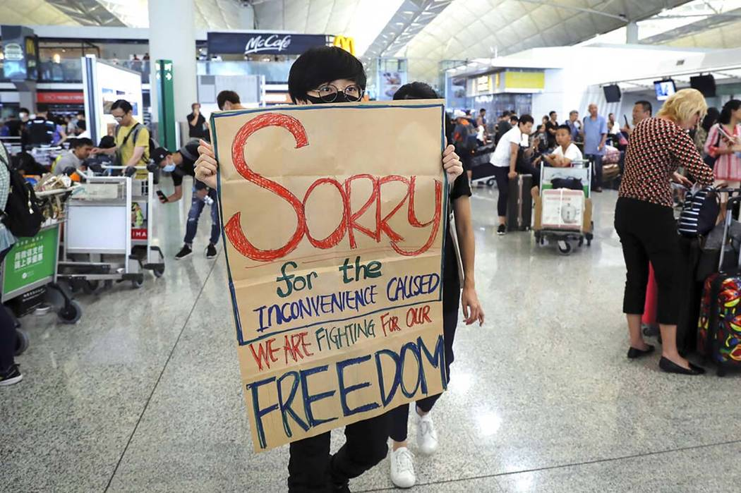 A protester shows a placard to stranded travelers during a demonstration at the Airport in Hong ...