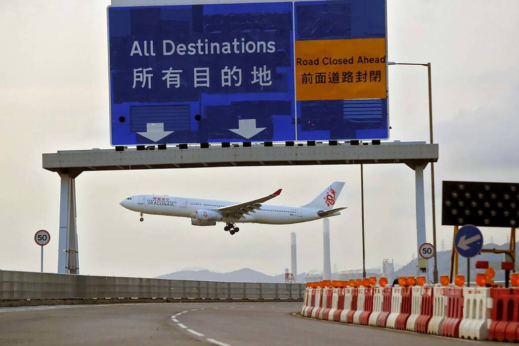 A Dragonair plane flies past a road sign at the airport in Hong Kong, Tuesday, Aug. 13, 2019. P ...