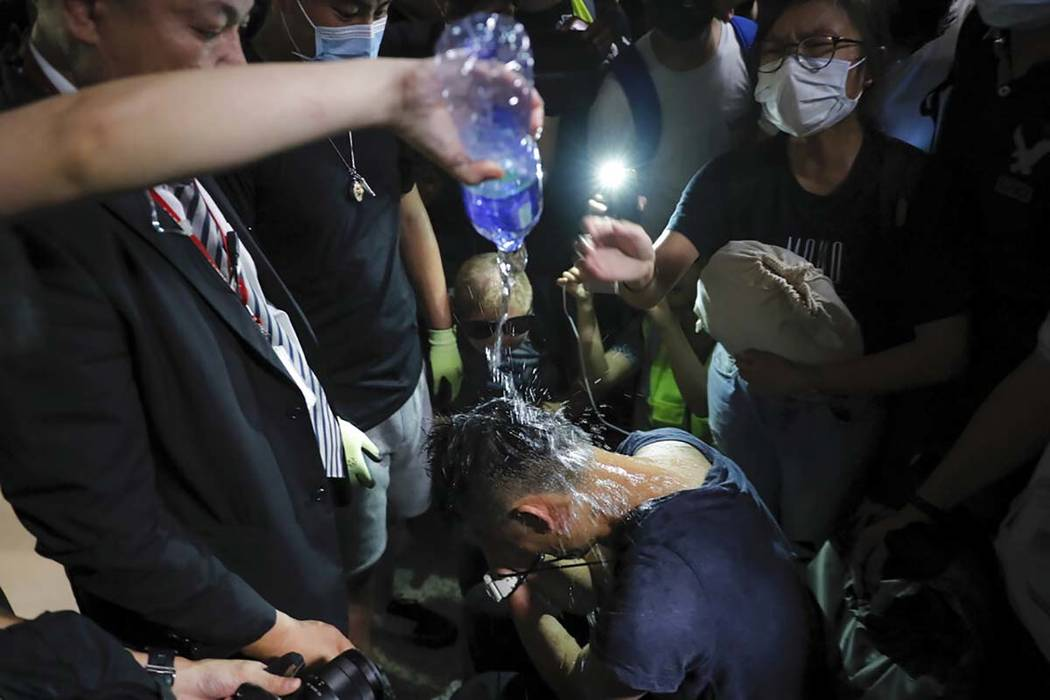 A protester pours water on a detained man, who protesters claimed was a police officer from mai ...