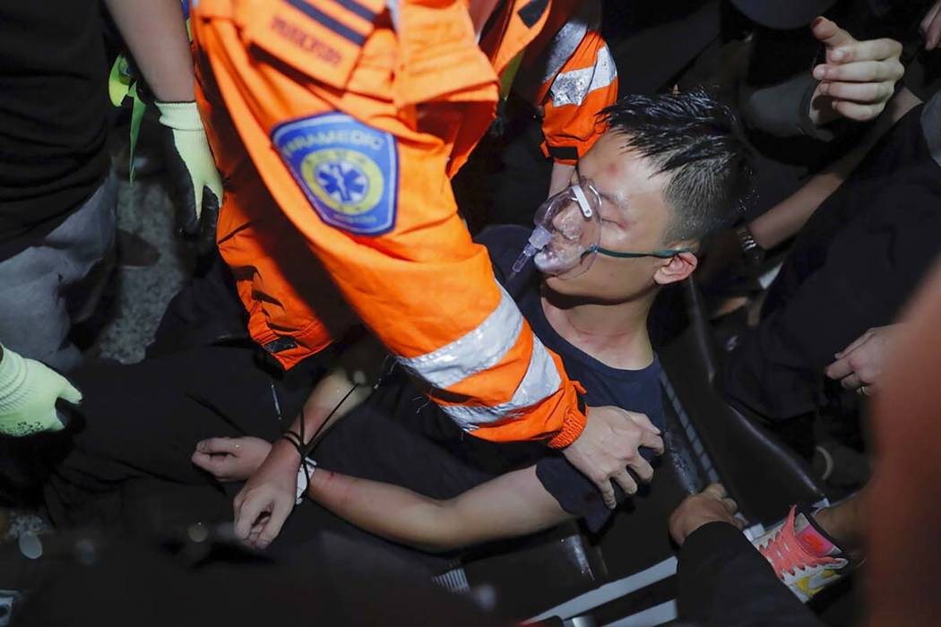 A medical staffer helps a detained man, who protesters claimed was a police officer from mainla ...