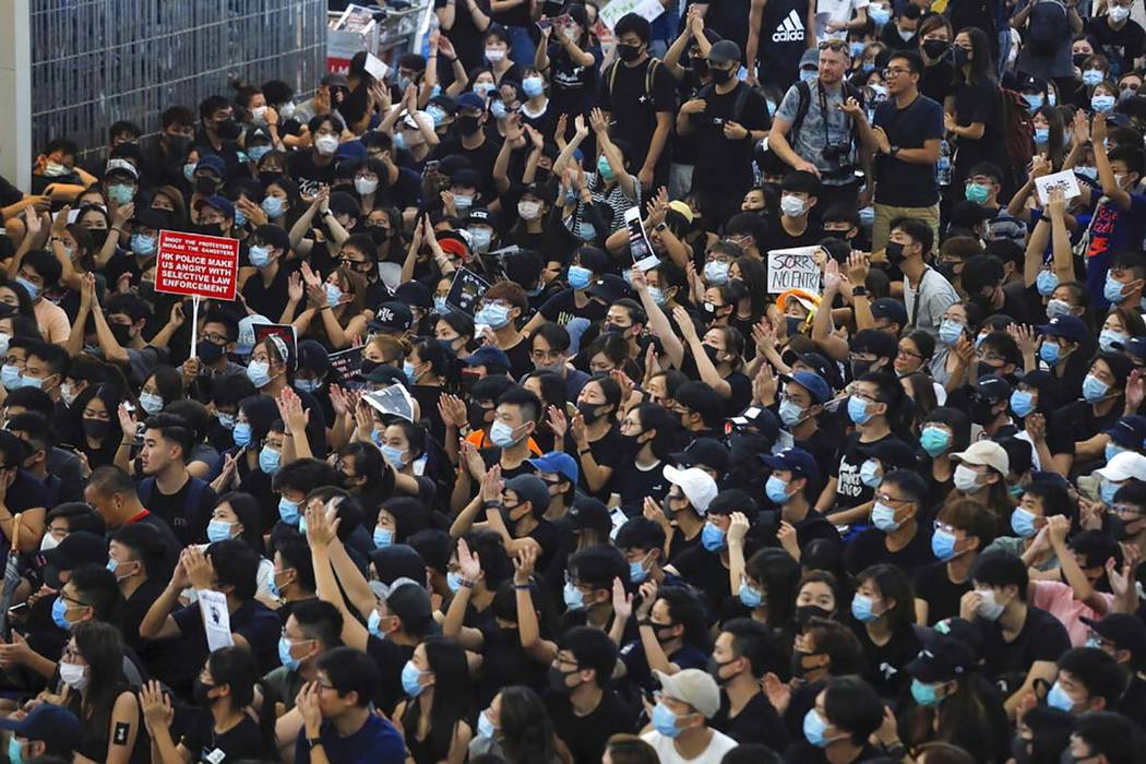 Protesters gesture as they stage a sit-in rally at the Airport in Hong Kong, Tuesday, Aug. 13, ...
