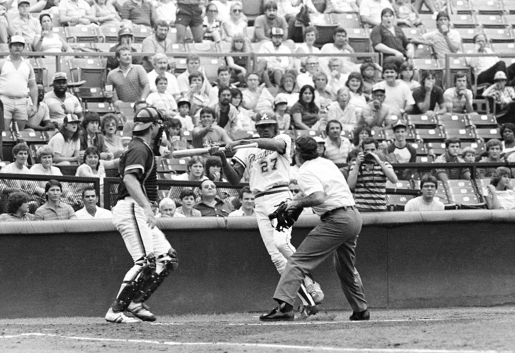 Home Plate umpire Steve Rippley blocks bat-swinging Atlanta Braves Pascual Perez in the second ...