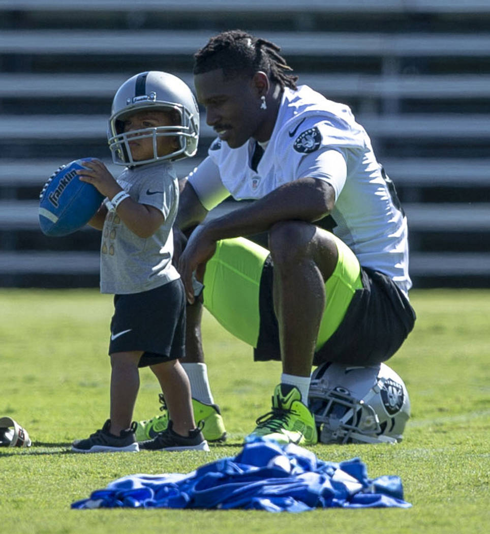 Oakland Raiders wide receiver Antonio Brown (84) plays on the sideline with his 23-month-old so ...