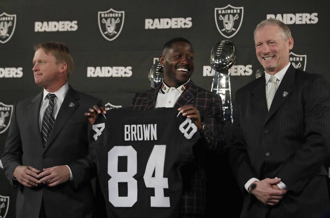 Oakland Raiders wide receiver Antonio Brown, center, holds his jersey beside coach Jon Gruden, ...